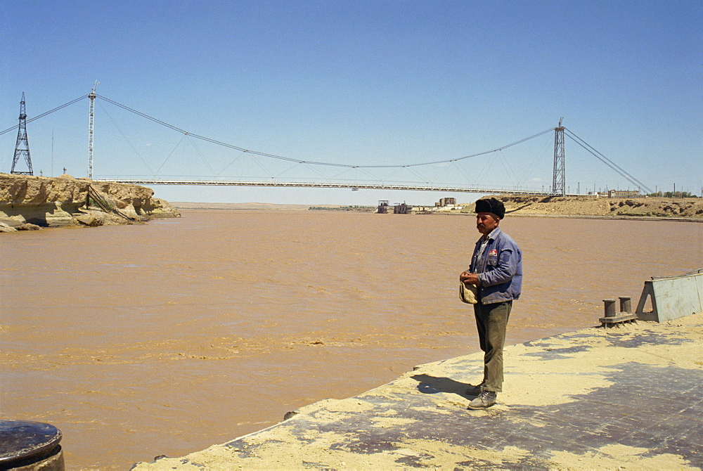 Man standing on the river bank in front of a bridge over the River Oxus (Amu Darya), between Uzbekistan and Turkmenia, Central Asia, Asia