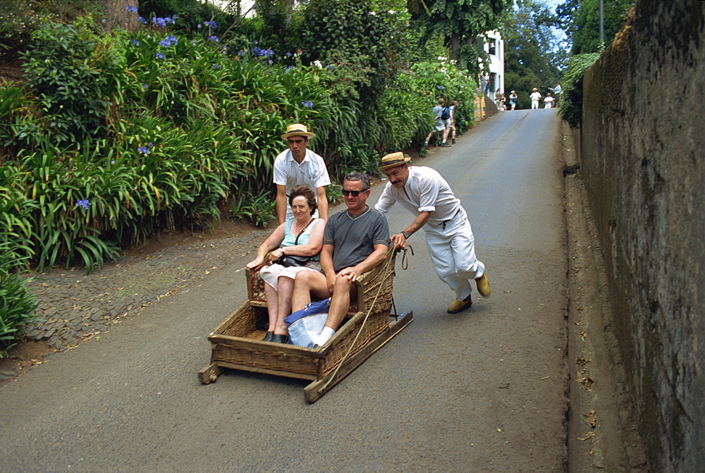 Tourists on toboggan riding down the hill at Monte, Madeira, Portugal, Europe