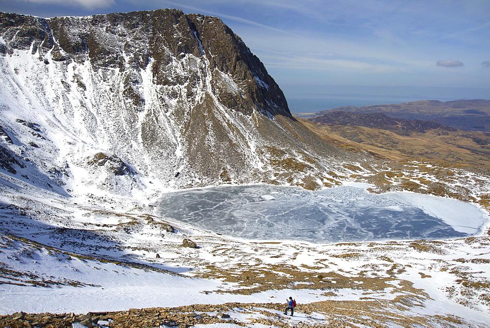 The frozen Llyn Y Gadair below summit of Cyfrwy, 811m, near Cadair Idris, Snowdonia National Park, Wales, United Kingdom, Europe