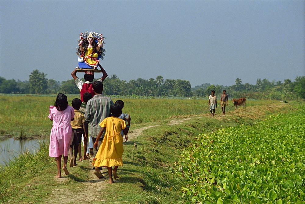 Group delivering Hindu god model to village, Parganas District, West Bengal, India, Asia