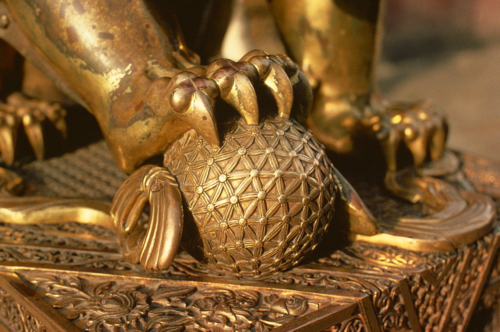 Close-up of the paw of a gilt bronze lion holding a fire ball, symbol of force, in the Forbidden City in Beijing, China, Asia