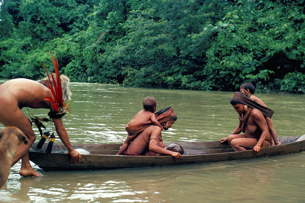 Yanomami crossing river in boat, Brazil, South America