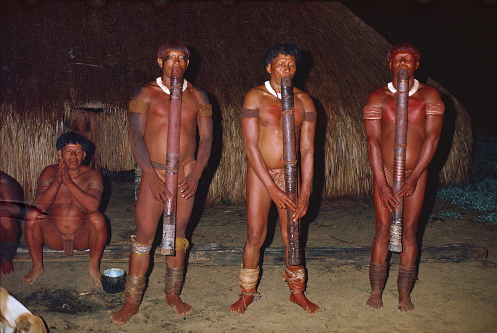 A group of Yawalapiti Indians playing Jabui flutes at night in Brazil, South America