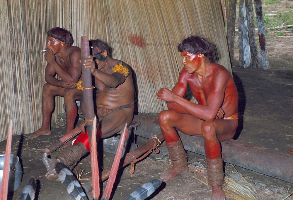 Kamayura Indians playing flutes inside hut, Xingu area, Brazil, South America