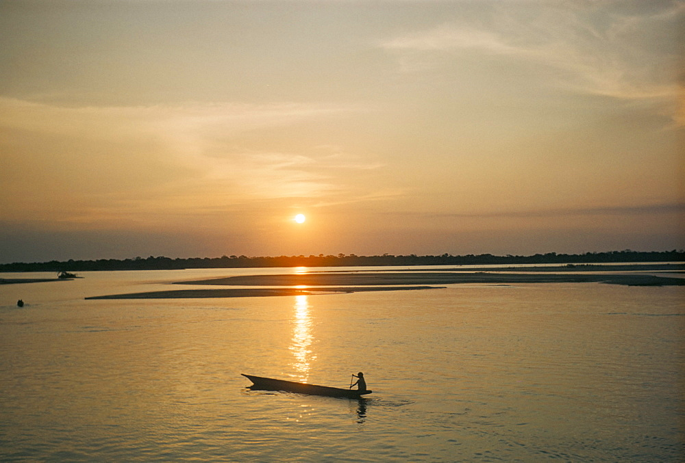 Sunset over Araguava River, Bananal and Karaja Indian in canoe, Brazil, South America