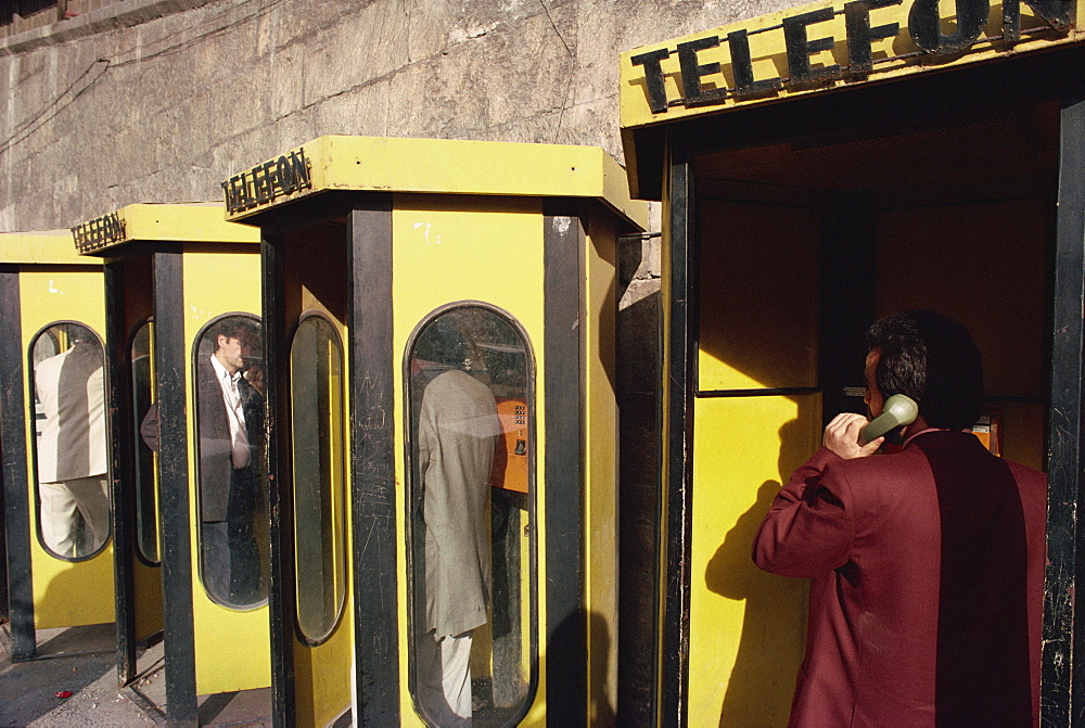 People in telephone kiosks on Galata Bridge, Istanbul, Turkey, Europe