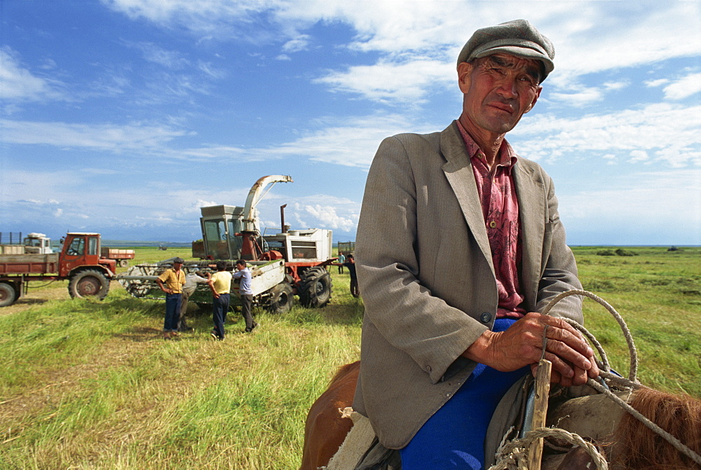 Portrait of a man, Anvar Tuunthush, a foreman, with farm machinery in the background on the north east shore of Lake Issyk-Kul, Kyrgyzstan, Central Asia, Asia