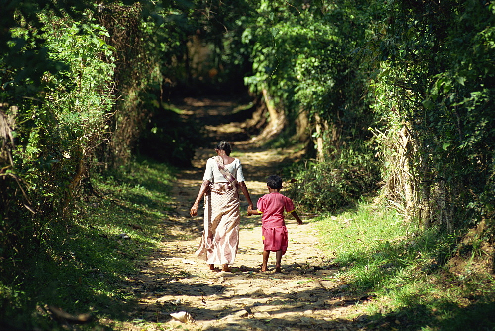 Grandmother and child walking up leafy avenue near Dambulla, Sri Lanka, Asia