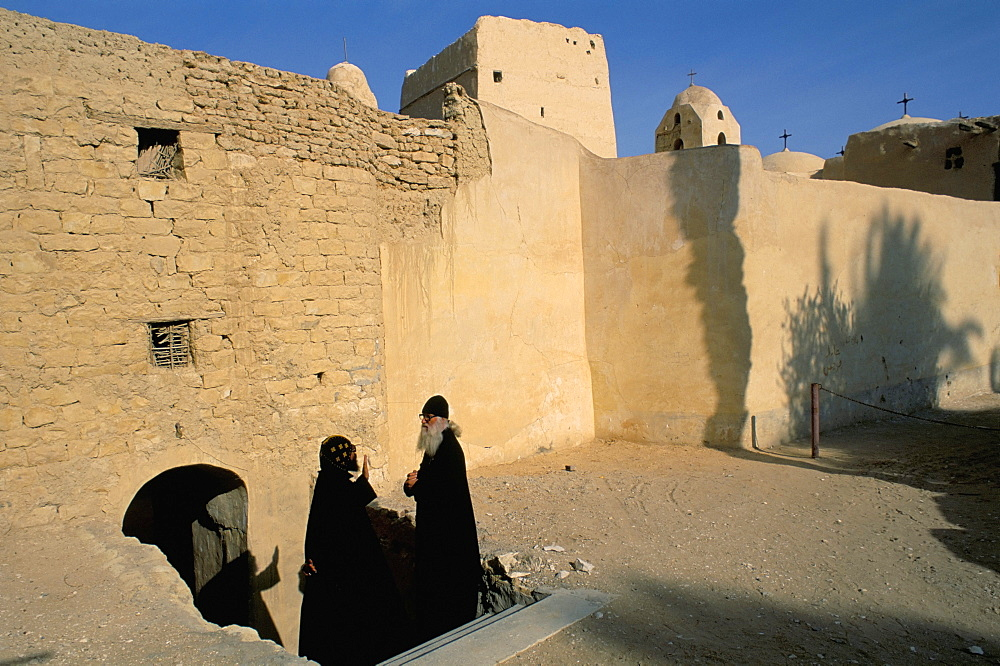 Monk and guest by monastery walls, St. Antony's (St. Anthony's) Coptic Monastery, Eastern Desert, Egypt, North Africa, Africa
