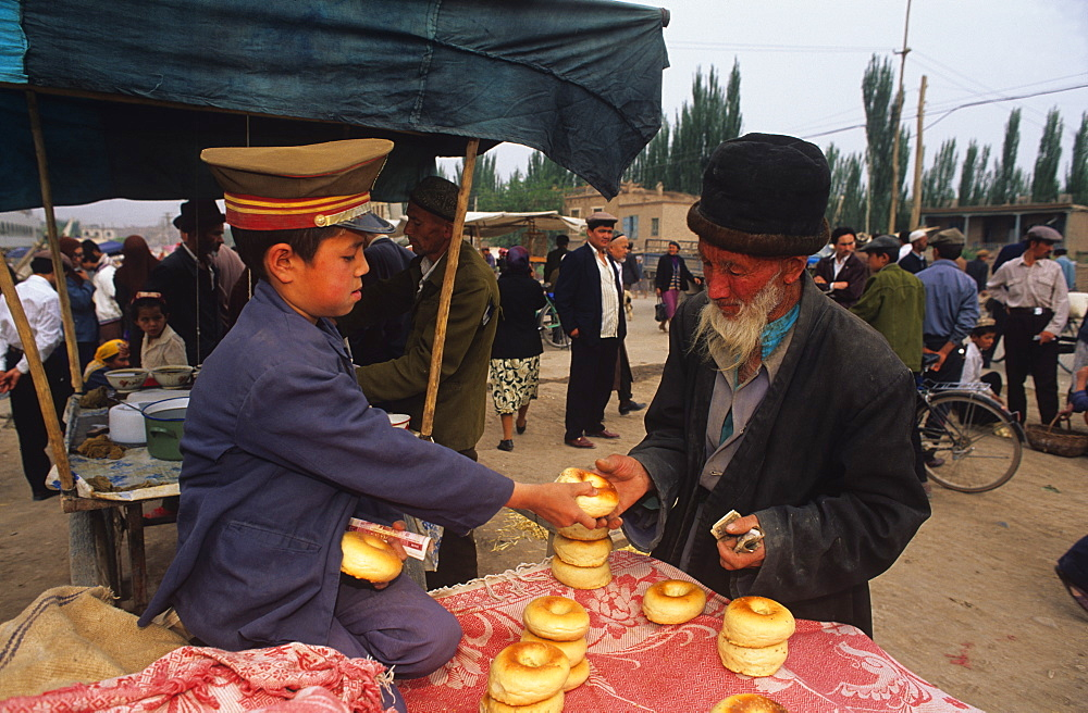 Buying bagel-like rolls, Sunday Market, Kashgar, Xinjiang, China, Asia