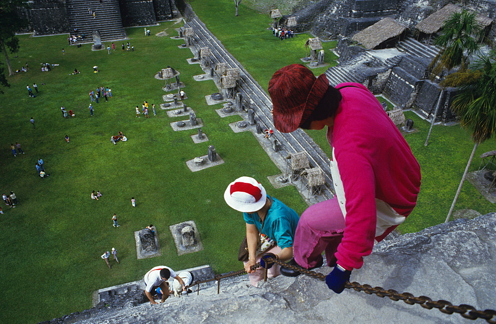Tourist climbing down front of Temple One, Tikal, UNESCO World Heritage Site, Guatemala, Central America
