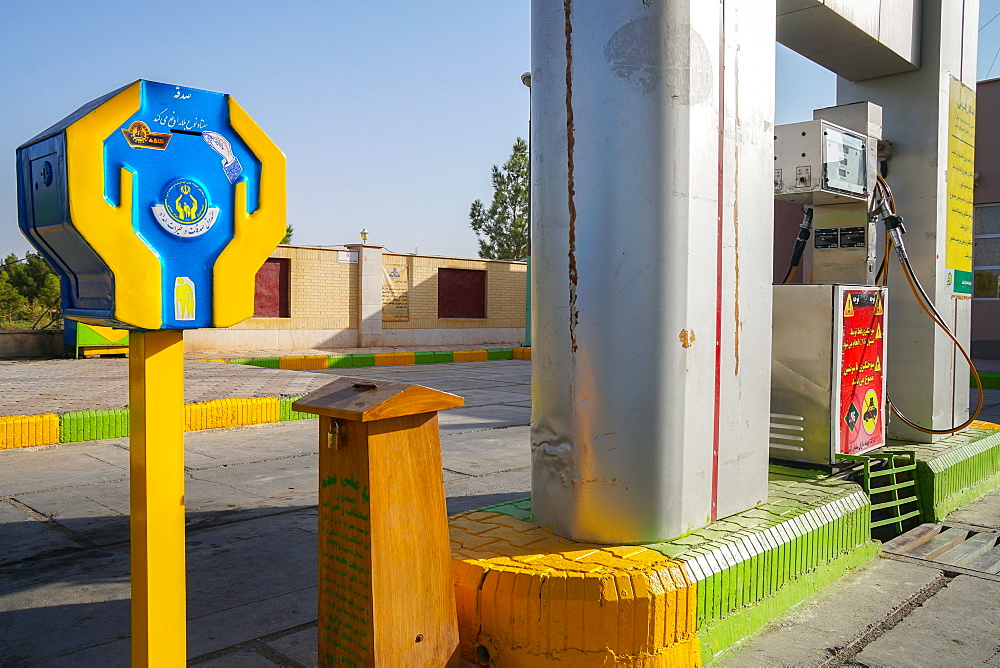 Two dominant themes of religion and oil meet at the petrol station, where there is always a religious donation box, Varzaneh, Iran, Middle East