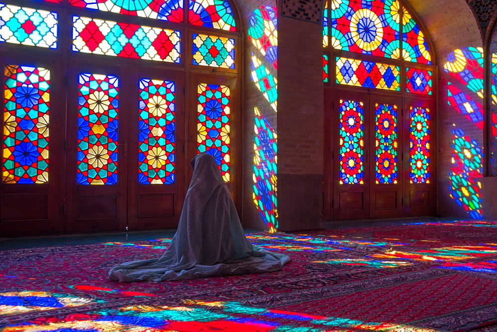 Worshipper in front of stained glass windows of Prayer Hall, Nasir-al Molk Mosque, Shiraz, Iran, Middle East
