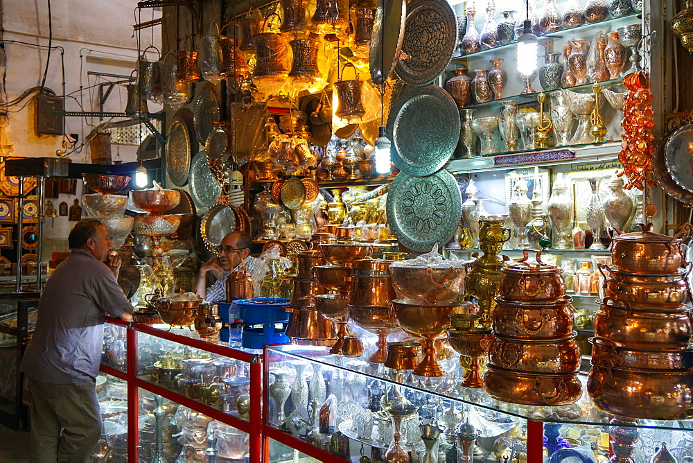 Two bazaaris chatting over the counter of a metalwork shop, Grand Bazaar, Isfahan, Iran, Middle East
