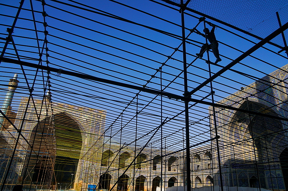 Silhouetted workman setting up marquee for special event in the courtyard of Imam Mosque, Isfahan, Iran, Middle East