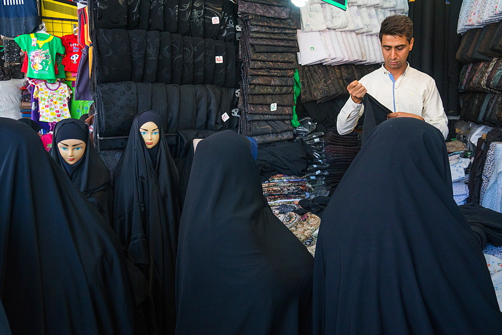 Chador merchant with customers and mannequins, bazaar, Qom, Iran, Middle East