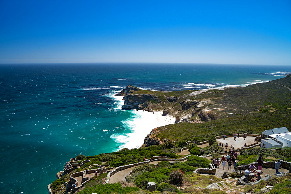 View back to the Cape Peninsula, with tourists walkning down from the lighthouse at Cape Point, near Cape Town, South Africa, Africa