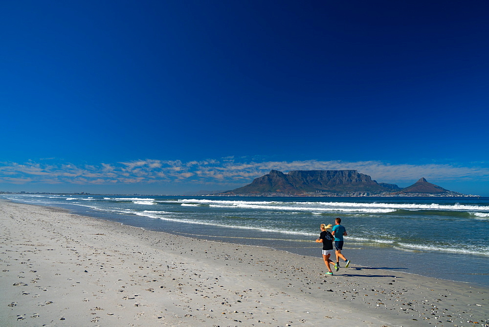 Joggers running on Blouberg Beach in the early morning, with Table Mountain in the background, Cape Town, South Africa