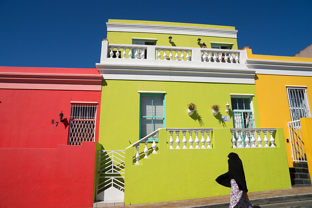 Silhouetted woman covered in black robe passes brightly coloured houses in Bo-Kaap, the Malaysian and Muslim area, Cape Town, South Africa, Africa - 450-4187