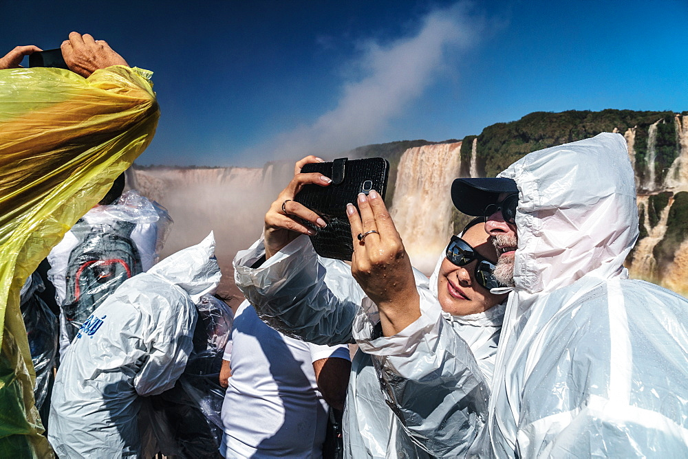 Selfie takers in plastic, Garganta del Diablo (Devil's Throat), Iguazu Falls, UNESCO World Heritage Site, Iguazu, Brazil, South America