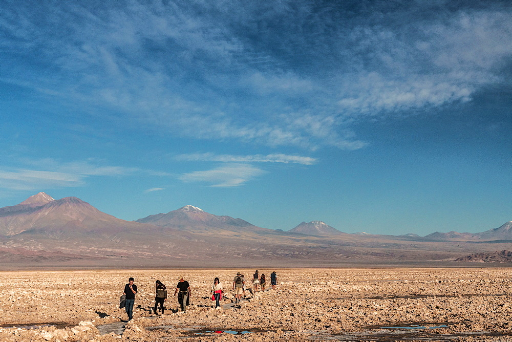 Hikers out on the Atacama Salt Flats, with snow-capped volcanic peaks in the background, near San Pedro de Atacama, Chile, South America