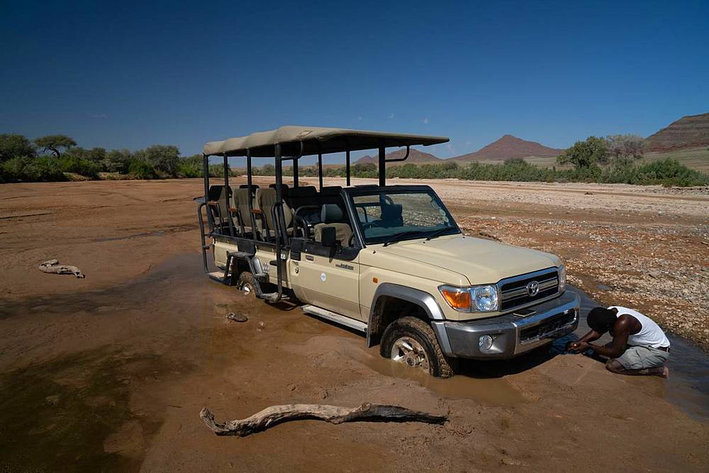 Guide tries to jack up safari vehicle stuck in the sand of Hoarusib Riverbed, Puros, north of Sesfontein, Nambia, Africa