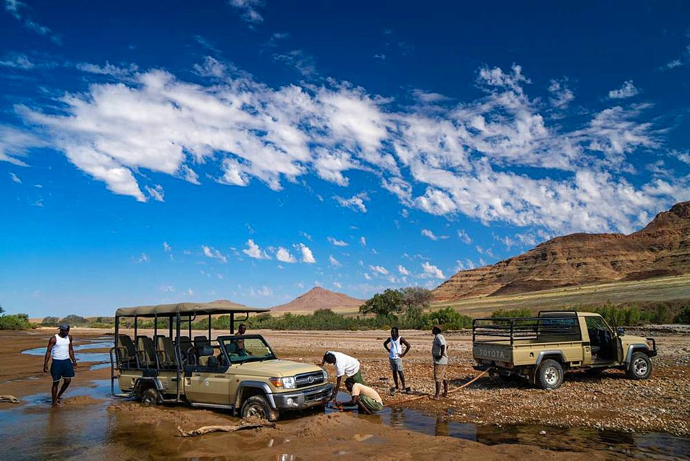 Rescuing safari vehicle stuck in sand of Hoarusib Riverbed, mountain range in background, Puros, north of Sesfontein, Namibia, Africa