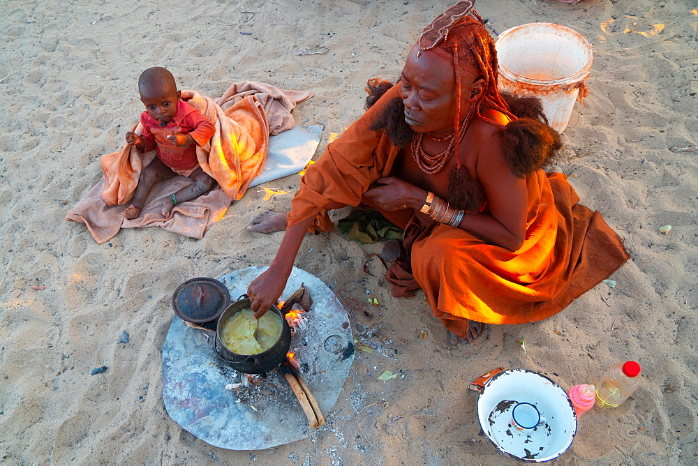 One senior red ochred Himba woman with her child cooking on an open fire, Puros Village, nearr Sesfontein, Namibia, Africa - 450-4365