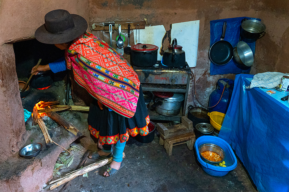 Local woman in colourful traditional dress cooks breakfast over an open fire, Chumbe Community, Lamay, Sacred Valley, Peru