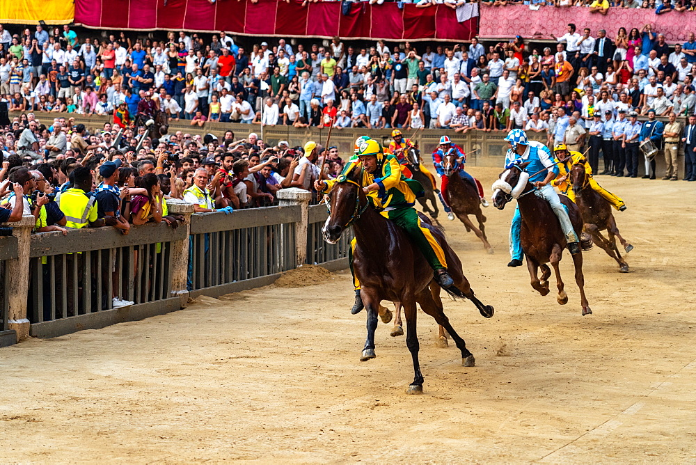 Jockeys in colourful outfits representing their respective neighbourhoods at full pelt at the Palio, a bareback horserace, Siena, Tuscany, Italy, Europe - 450-4428