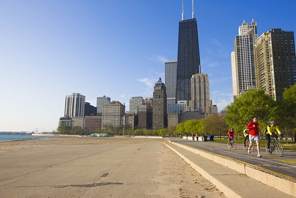 Joggers and cyclists on Lake Michigan shore with the Near North skyline behind, Oak Street Beach, Chicago, Illinois, United States of America, North America