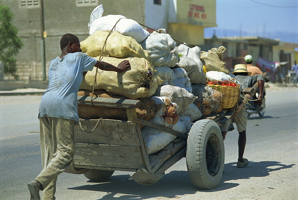 Men pushing and pulling heavily loaded cart along road, Port au Prince, Haiti, West Indies, Caribbean, Central America