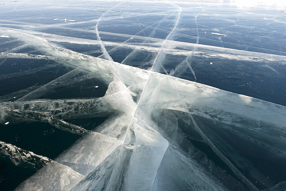 Pressure cracks appear in the 80cm thick clear black ice on the surface of the 800m deep frozen Lake Baikal, Irkutsk Oblast, Siberia, Russia, Eurasia
