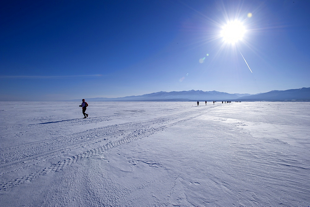 Runners in the 10th Baikal Ice marathon, run on the frozen surface of the world's largest fresh water lake on March 1st 2014, Siberia, Russia, Eurasia