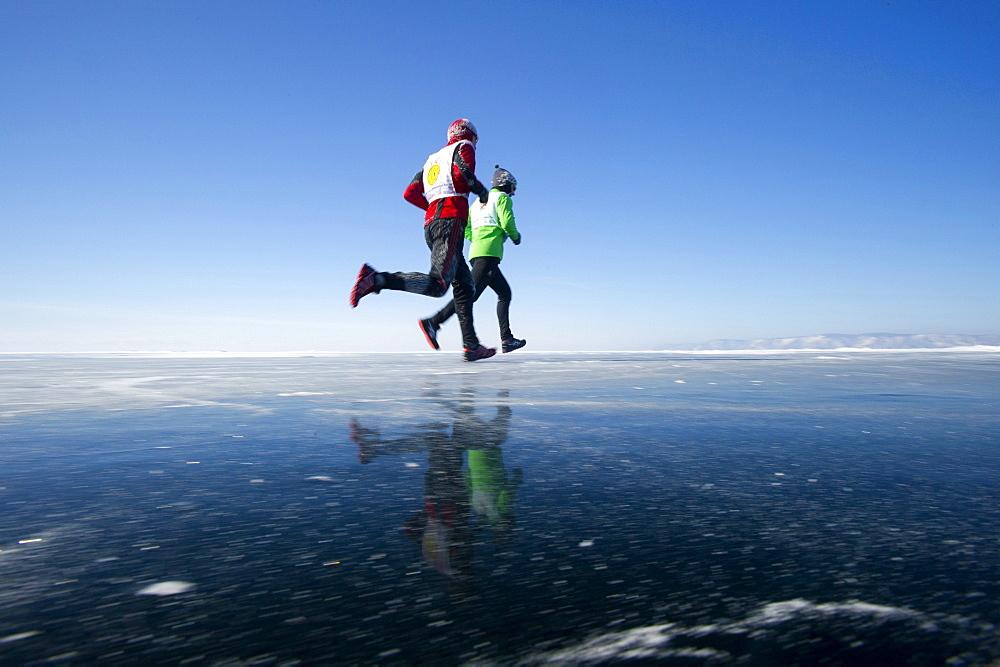 Runners in the 10th Baikal Ice Marathon, run on the frozen surface of the world's largest fresh water lake on 1st March 2014, Siberia, Irkutsk Oblast, Russia, Eurasia