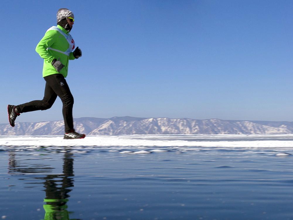 Runner in the 10th Baikal Ice Marathon, run on the frozen surface of the world's largest fresh water lake on 1st March 2014, Siberia, Irkutsk Oblast, Russia, Eurasia