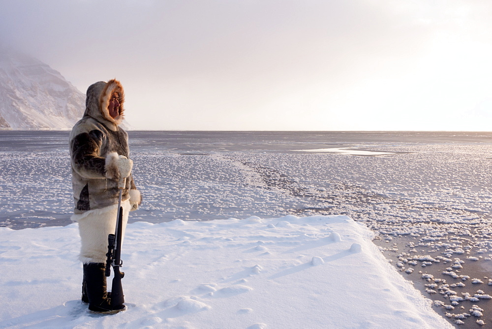 One of the last remaining Inughuit subsistence hunters, Naimanngitsoq Kristiansen, stands on watch with his rifle for marine mammals at the ice edge, Greenland, Denmark, Polar Regions