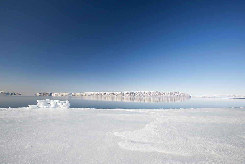 Hunting blind made from ice blocks at the Floe edge, the junction of sea ice and the ocean, Herbert Island in the background, Greenland, Denmark, Polar Regions