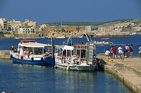Tourists boarding boats from a jetty in St. Pauls Bay, Malta, Mediterranean, Europe
