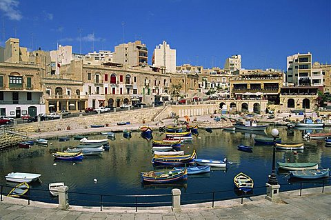 Boats and buildings on the waterfront at St. Julians Bay on the island of Malta, Mediterranean, Europe