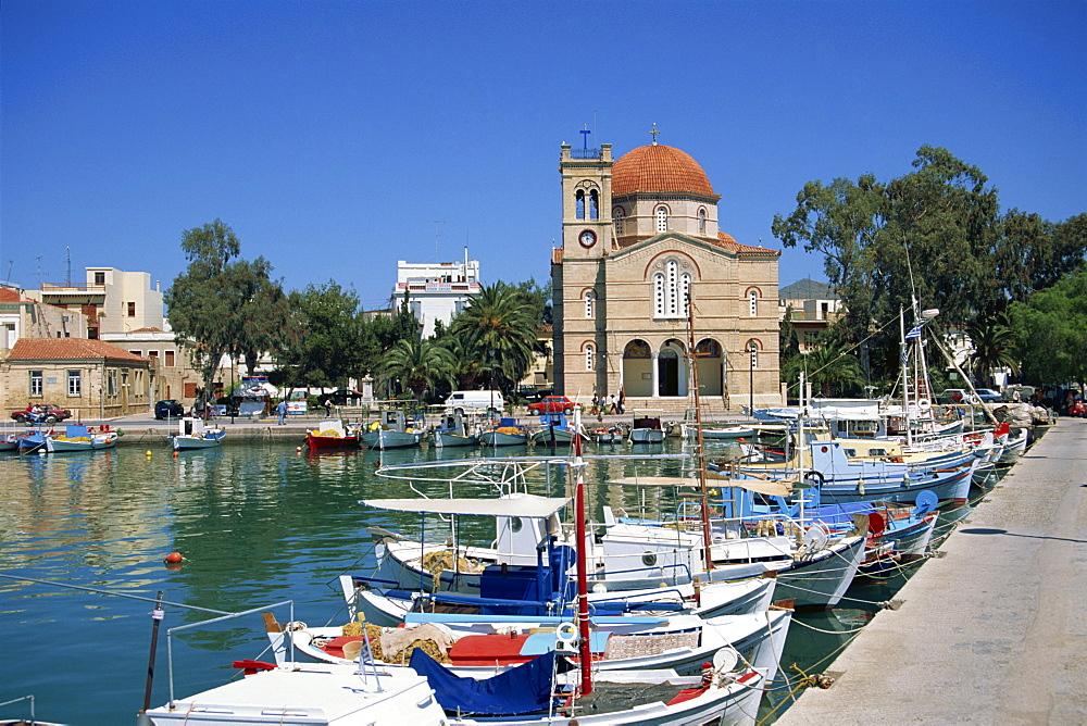 Fishing boats moored in harbour and domed church, Aegina Town, Aegina, Saronic Islands, Greek Islands, Greece, Europe