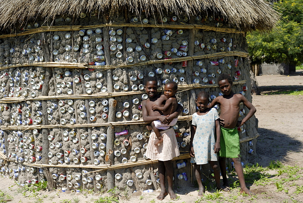 Recycling tins in traditional house building, and children, Botswana, Africa