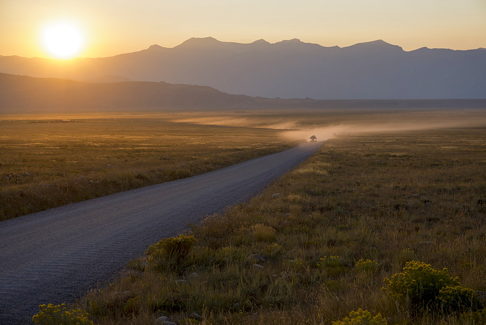 Car on dusty road at sunset, Grand Teton Park, Wyoming, United States of America, North America - 483-2123