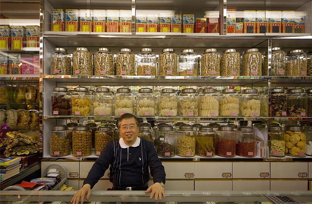 Man standing behind counter of a grocery shop, looking at camera, Hong Kong, China, Asia
