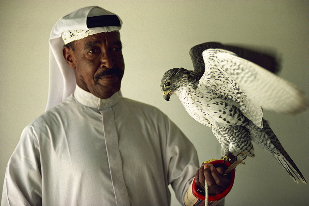 Portrait of falcon handler and Gyr Falcon, Bahrain, Middle East