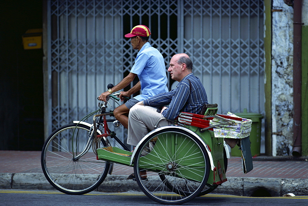 Western man riding as passenger in a cycle rickshaw in Singapore, Southeast Asia, Asia