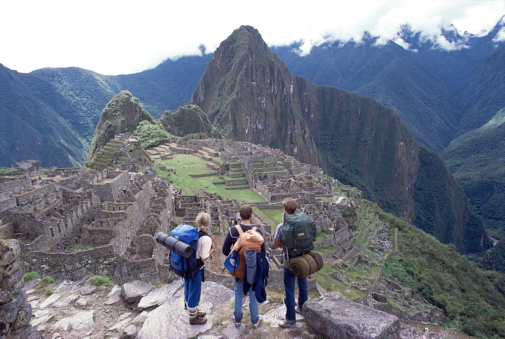 Backpackers at the Inca ruins of Machu Picchu, with Huayna Picchu in background, Peru, South America