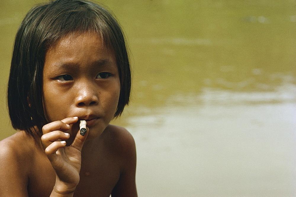 Kayan child smoking, along the Balui River, Sarawak, Malaysia, Southeast Asia, Asia - 54-2201