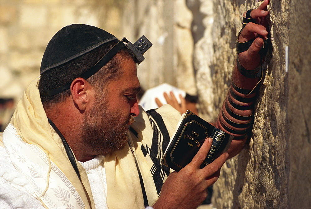 Close-up of Jew wearing shawl, skull cap and phylactery and holding a book, praying at the Western Wall in Jerusalem, Israel, Middle East