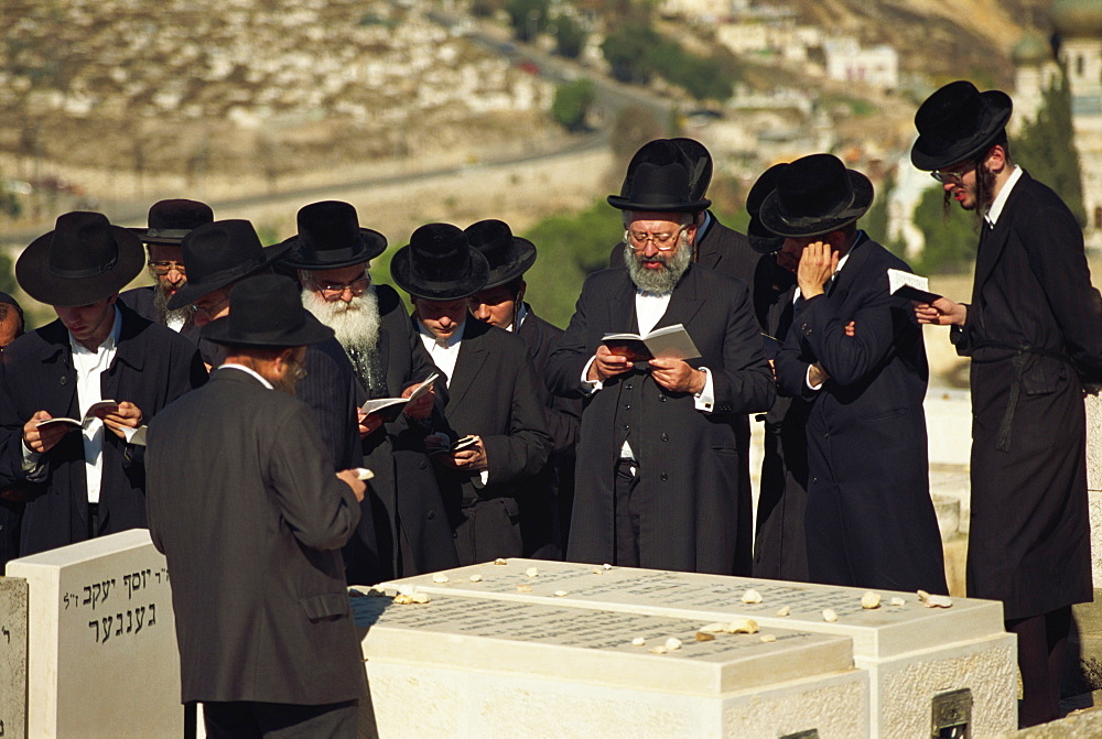 Orthodox Jews praying on a tomb on the Mount of Olives, in Jerusalem, Israel, Middle East